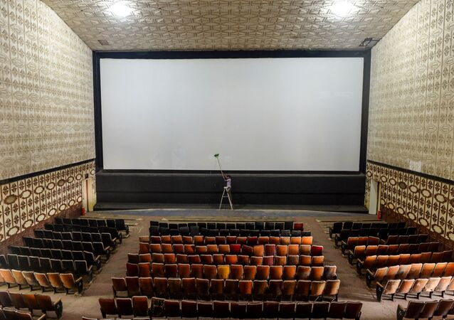 A worker cleans the screen of a cinema hall as part of preparations for a possible reopening after the government eased the lockdown restrictions previously imposed due to the Covid-19 coronavirus, in Chennai on October 8, 2020