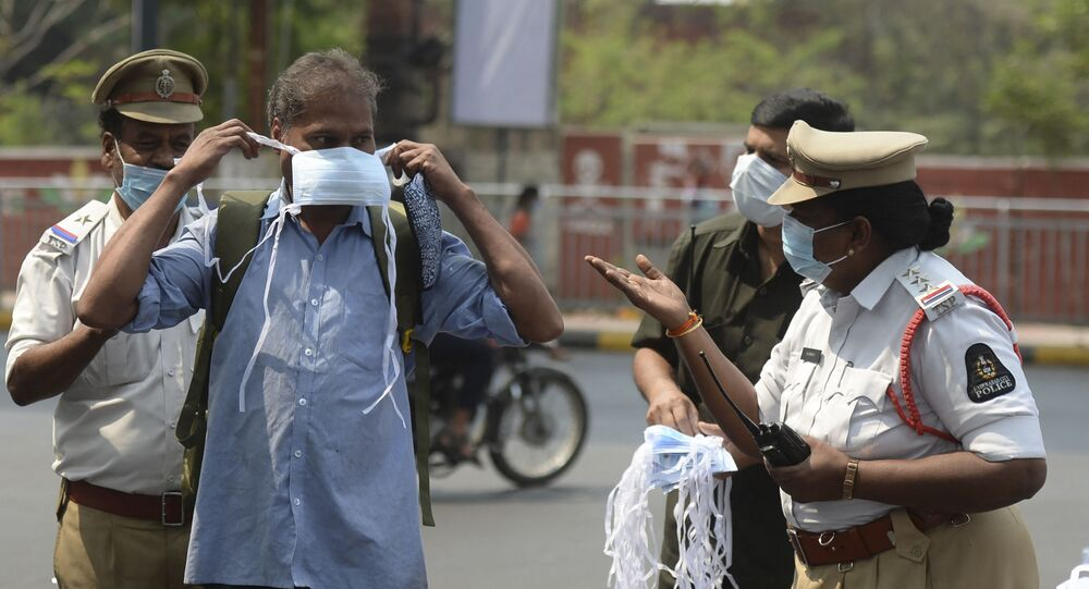 A female police officer urges a man to wear a face mask during an awareness campaign against the spread of the COVID-19 coronavirus on World Health Day, at a traffic junction in Hyderabad on 7 April 2021.