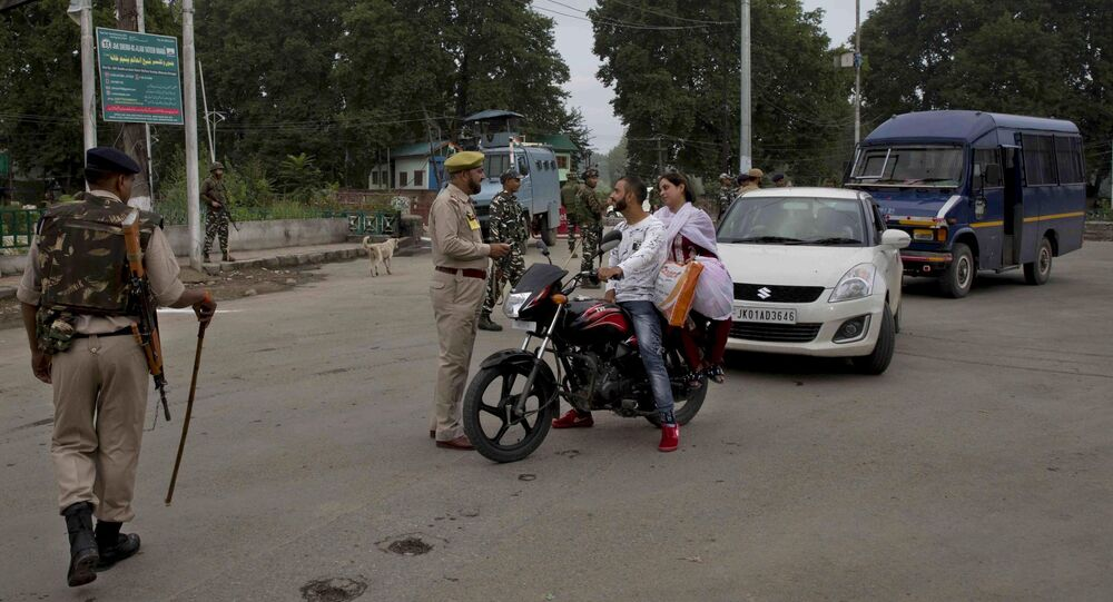 An Indian police man interrogates a Kashmiri couple before turning them back at a checkpoint during security lockdown in Srinagar, Indian controlled Kashmir, Thursday, Aug. 15, 2019