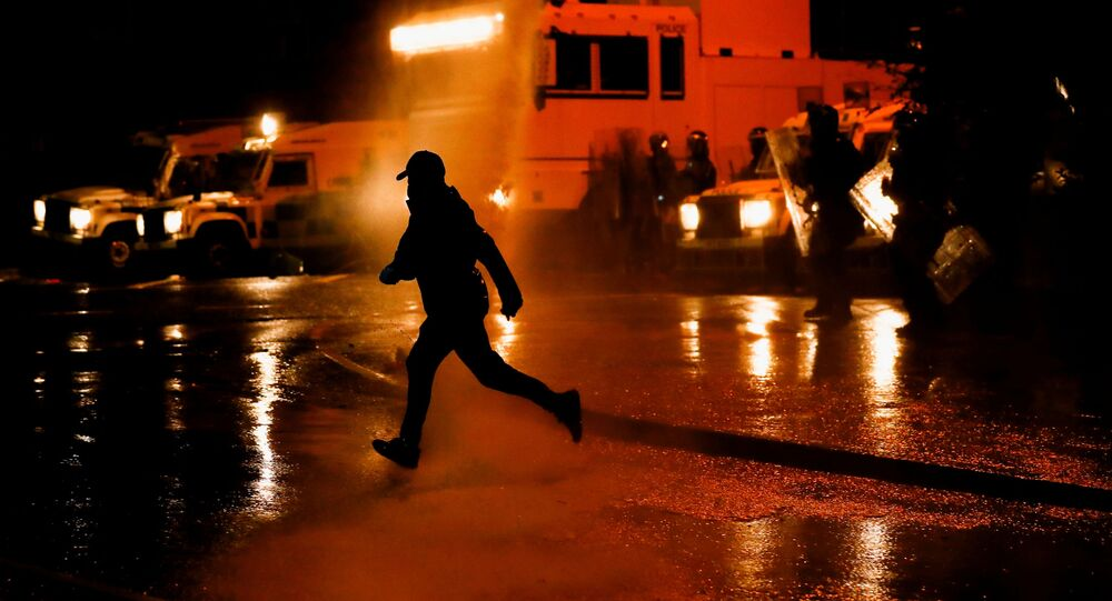 A rioter reacts as the police use a water cannon on Springfield Road as protests continue in Belfast, Northern Ireland April 8, 2021.