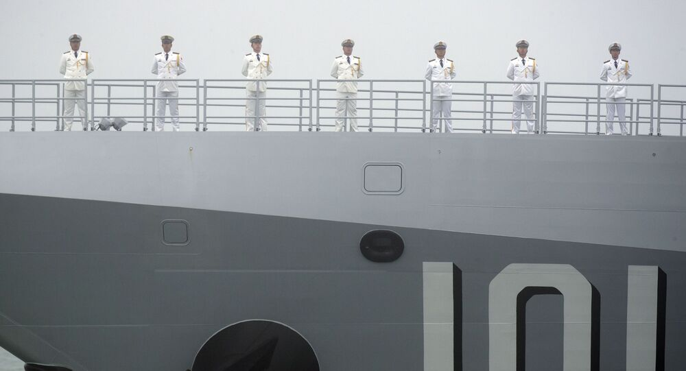 Sailors stand on the deck of the new type 055 guided-missile destroyer Nanchang of the Chinese People's Liberation Army (PLA) Navy as it participates in a naval parade to commemorate the 70th anniversary of the founding of China's PLA Navy in the sea near Qingdao in eastern China's Shandong province, Tuesday, 23 April 2019