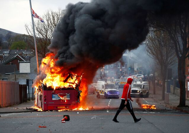 A man walks past a hijacked bus burning on The Shankill Road as protests continue in Belfast, Northern Ireland, 7 April 2021.