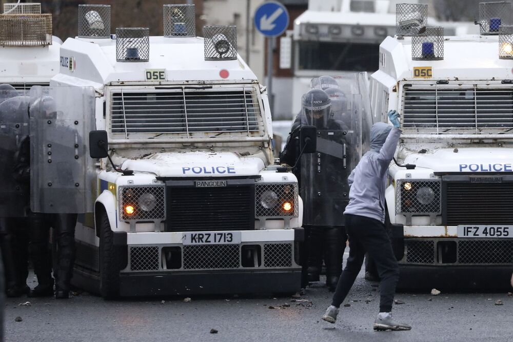 A Nationalist youth prepares to throw something at a police line blocking a road near the Peace Wall in West Belfast, Northern Ireland, Thursday, 8 April 2021. Authorities in Northern Ireland sought to restore calm Thursday after Protestant and Catholic youths in Belfast hurled bricks, fireworks and gasoline bombs at police and each other. It was the worst mayhem in a week of street violence in the region, where Britain's exit from the European Union has unsettled an uneasy political balance.