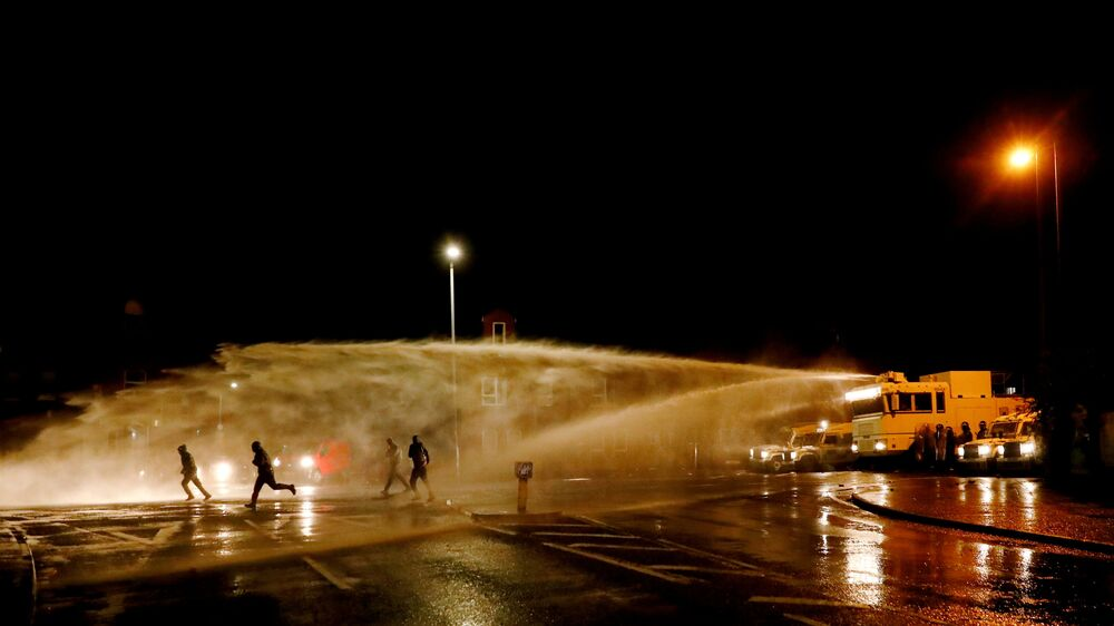 Rioters react as police use a water cannon on the Springfield Road as protests continue in Belfast, Northern Ireland 8 April 2021.