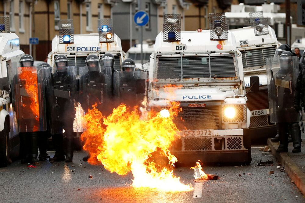 A fire burns in front of the police on the Springfield Road as protests continue in Belfast, Northern Ireland 8 April 2021.