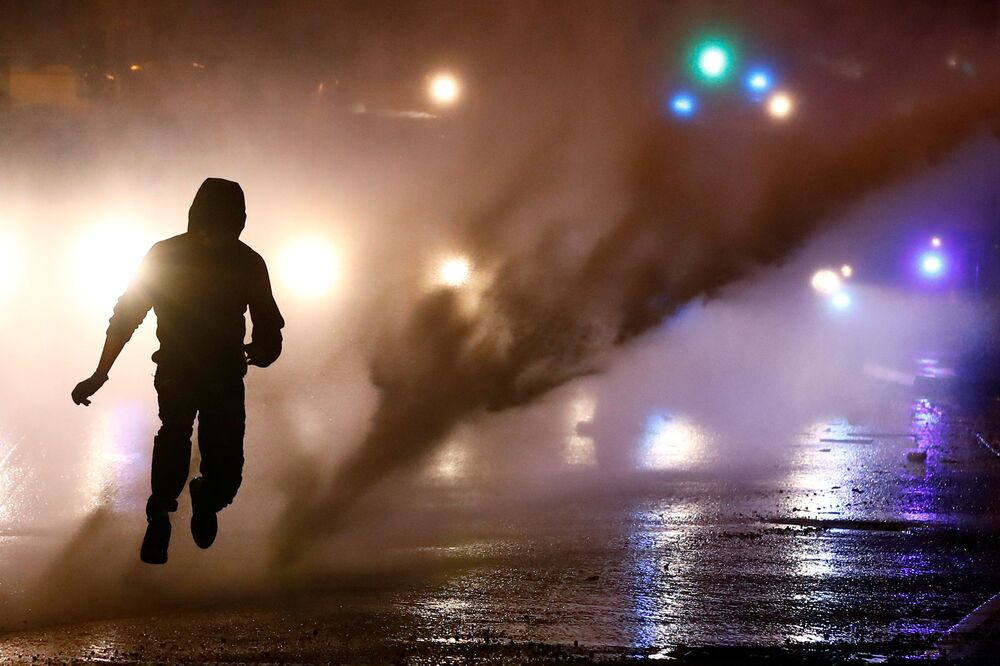 A rioter reacts as the police uses a water cannon on the Springfield Road as protests continue in Belfast, Northern Ireland 8 April 2021.