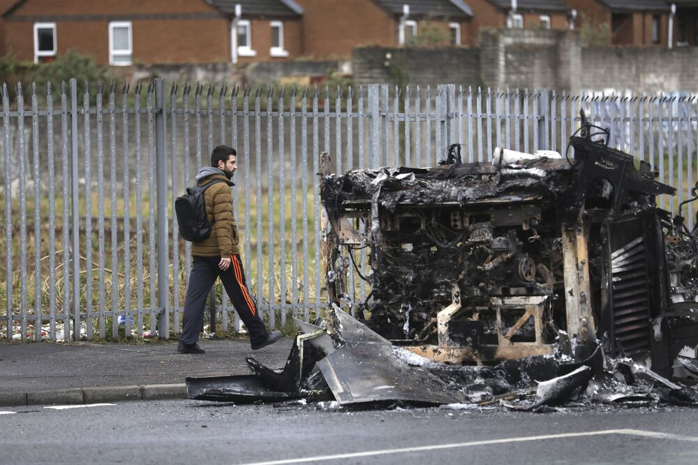 A man walks past a burnt out bus on the Shankill Road in West Belfast, Northern Ireland, Thursday, 8 April 2021. The scene follows another night of violence in Loyalist areas that has now spread to interface areas of the peace divide.