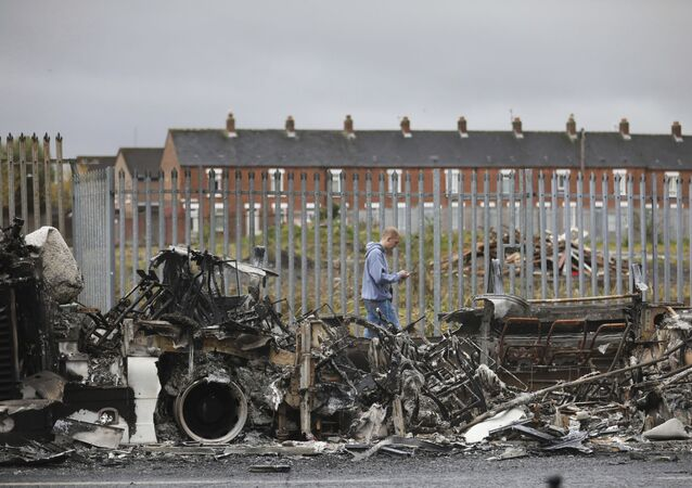 A man walks past a burnt out bus near the Shankill Road in west Belfast.