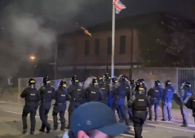 Screenshot from a video showing a stand-off between the protesters and police officers in Belfast, Northern Ireland