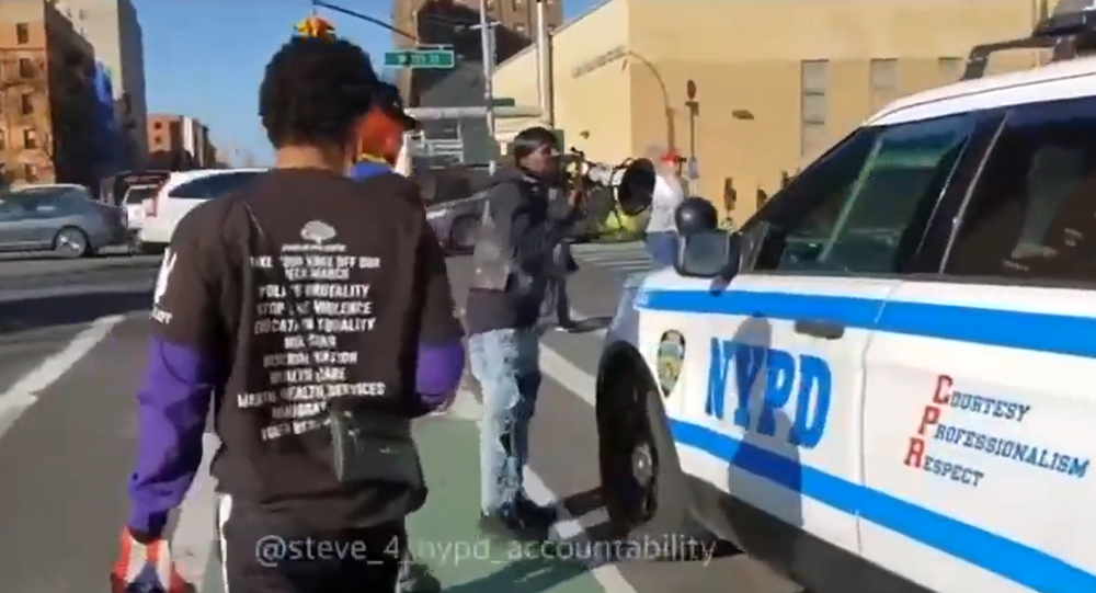 Screenshot from a video showing a group of men harassing New York Police Department officers who are driving by in an SUV