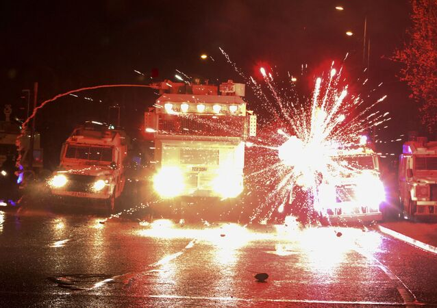 Fireworks explode at police vehicles after being fired at police officers with a water cannon during clashes with nationalist youths in the Springfield Road area of Belfast on April 8, 2021 as disorder continued in the Northern Ireland capital following days of mainly loyalist violence. (Photo by Paul Faith / AFP)