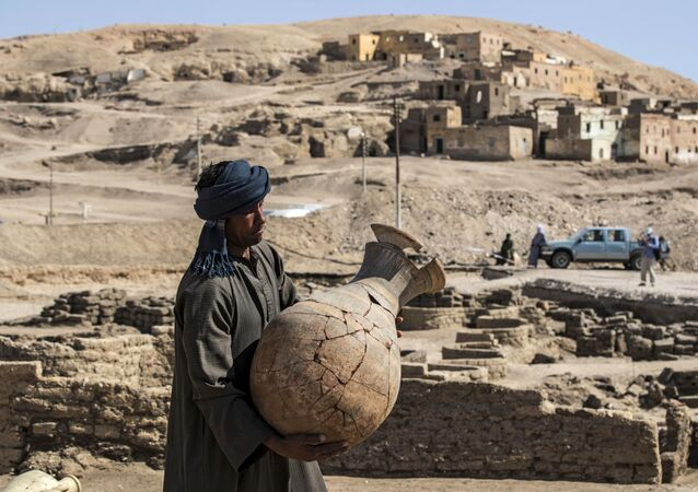 A picture taken on April 10, 2021, shows a worker carrying a pot at the archaeological site of a 3000 year old city, dubbed The Rise of Aten, dating to the reign of Amenhotep III, uncovered by the Egyptian mission near Luxor. - Archaeologists have uncovered the remains of an ancient city in the desert outside Luxor that they say is the largest ever found in Egypt and dates back to a golden age of the pharaohs 3,000 years ago. Famed Egyptologist Zahi Hawass announced the discovery of the lost golden city, saying the site was uncovered near Luxor, home of the legendary Valley of the Kings.