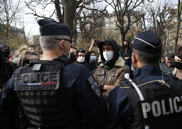 A man faces police officers during a counter-protest while supporters of the group Generation Identity demonstrate, Saturday, Feb. 20, 2021 in Paris. Supporters of Europe's extreme-right, anti-migrant movement Generation Identity protest against French government efforts to shut it down as a racist militia.