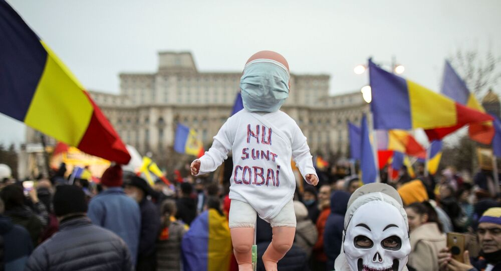 A man wearing a skull mask while dressed in white protection gear holds a baby doll with the message I am not a lab rat during a protest against mandatory mask wearing and coronavirus disease (COVID-19) vaccination, near the Romanian Parliament, in Bucharest, Romania March 20, 2021.