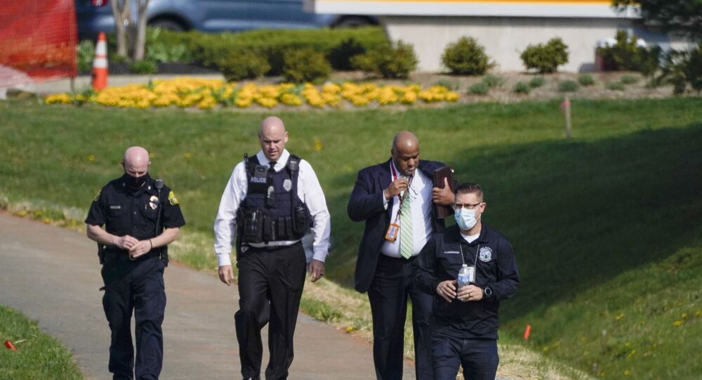 Police walk near the scene of a shooting at a business park in Frederick, Md., Tuesday, April 6, 2021.