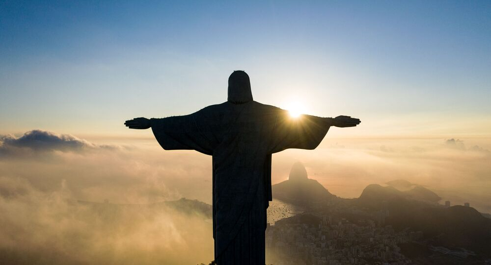 The sun rises in front of the Christ the Redeemer statue in Rio de Janeiro on March 24, 2021. - Christ the Redeemer is celebrating its 90th anniversary in October 2021 and is receiving restoration work to ensure that it looks its best for the public and visiting tourists.