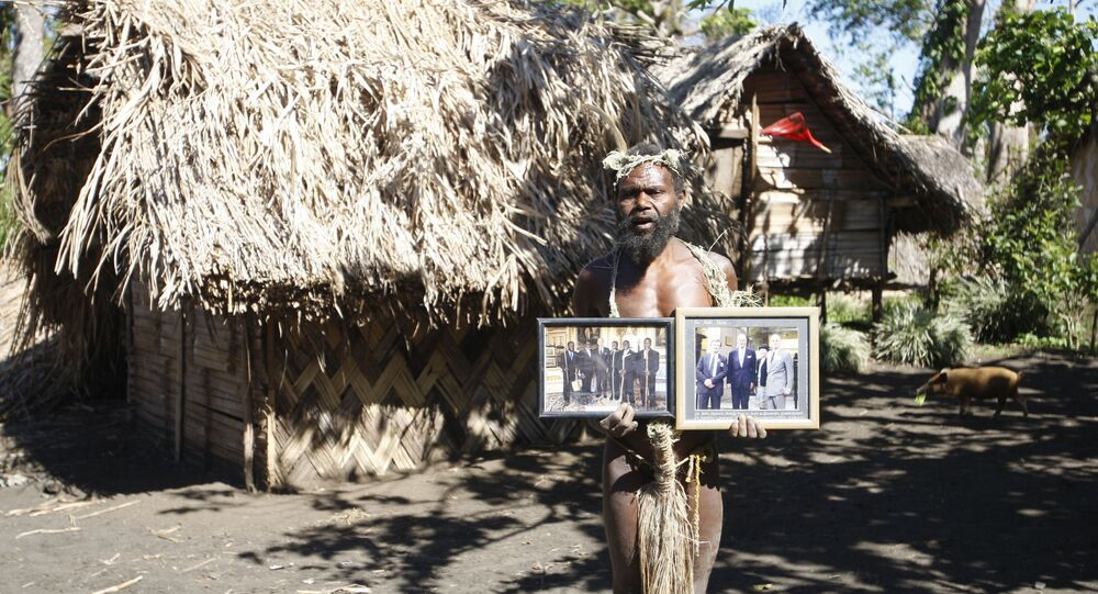 Albi Nagia poses with photographs of Prince Philip in Yakel, Tanna island, Vanuatu. Nagia is part of a movement which worships the prince as the son of their ancestral God.