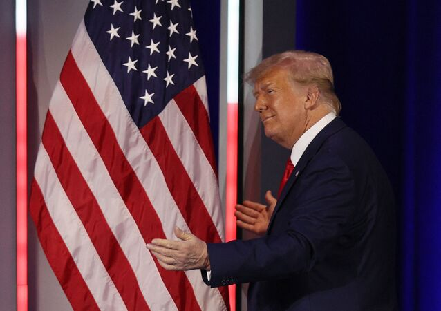 Former President Donald Trump embraces the American flag as he arrives on stage to address the Conservative Political Action Conference held in the Hyatt Regency on 28 February 2021 in Orlando, Florida. Joe Raedle/Getty Images/AFP (Photo by JOE RAEDLE / GETTY IMAGES NORTH AMERICA / Getty Images via AFP)