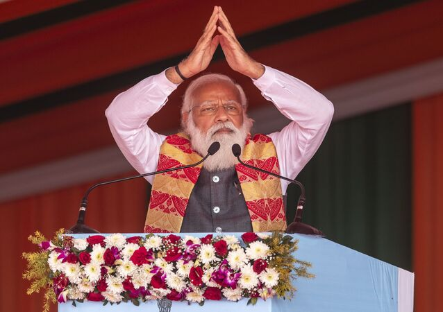 Indian Prime Minister Narendra Modi greets the crowd as he speaks during a public rally in Dhekiajuli, Assam, India, Sunday, Feb. 7, 2021.