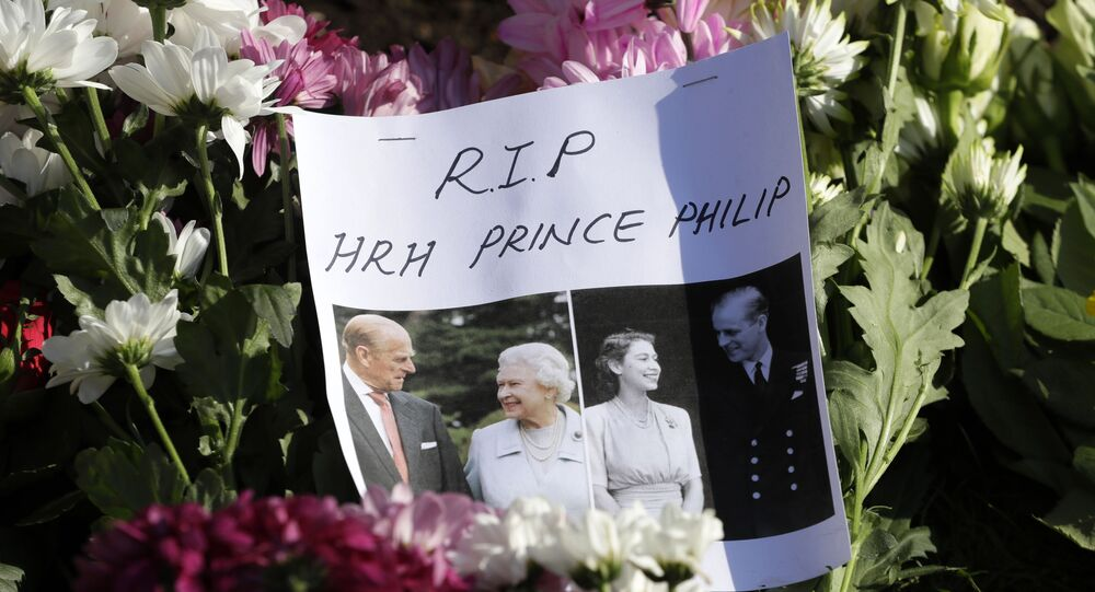 A message is left amoungst flowers outside Windsor Castle in Windsor, England Sunday, April 11, 2021. Britain's Prince Philip, the irascible and tough-minded husband of Queen Elizabeth II who spent more than seven decades supporting his wife in a role that mostly defined his life, died on Friday.