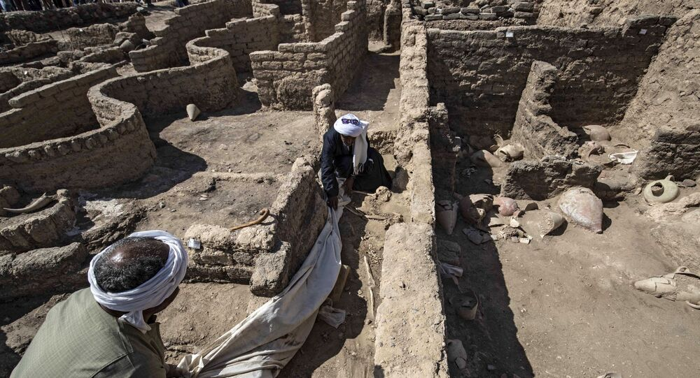 A picture taken on April 10, 2021, shows workers at the archaeological site of a 3000 year old city, dubbed The Rise of Aten, dating to the reign of Amenhotep III, uncovered by the Egyptian mission near Luxor. - Archaeologists have uncovered the remains of an ancient city in the desert outside Luxor that they say is the largest ever found in Egypt and dates back to a golden age of the pharaohs 3,000 years ago. Famed Egyptologist Zahi Hawass announced the discovery of the lost golden city, saying the site was uncovered near Luxor, home of the legendary Valley of the Kings.