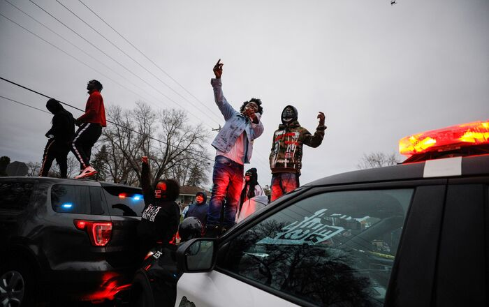 Demonstrators stand on a police vehicle during a protest after police allegedly shot and killed a man, who local media report is identified by the victim's mother as Daunte Wright, in Brooklyn Center, Minnesota, U.S.