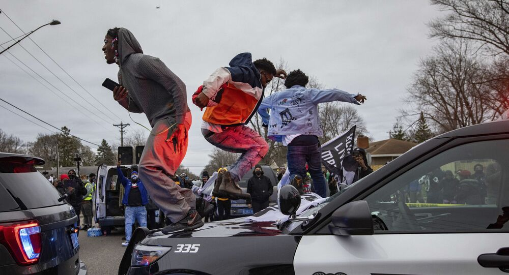 Men jump on the hood of a police car after a family said a man was shot and killed by law enforcement on Sunday, April 11, 2021, in Brooklyn Center, Minn.