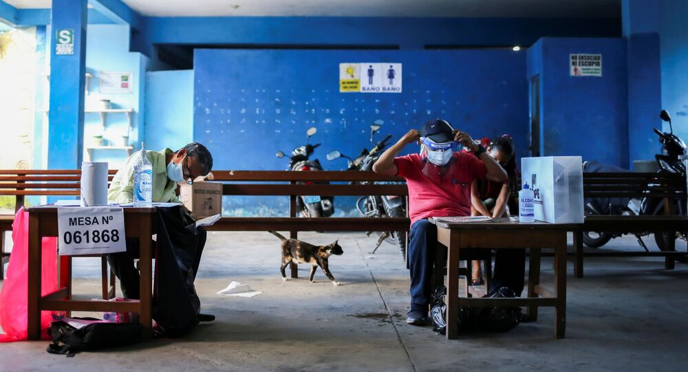 Electoral workers sit at their desks during the presidential and parliamentary elections, at a polling station in Belen, Peru April 11, 2021