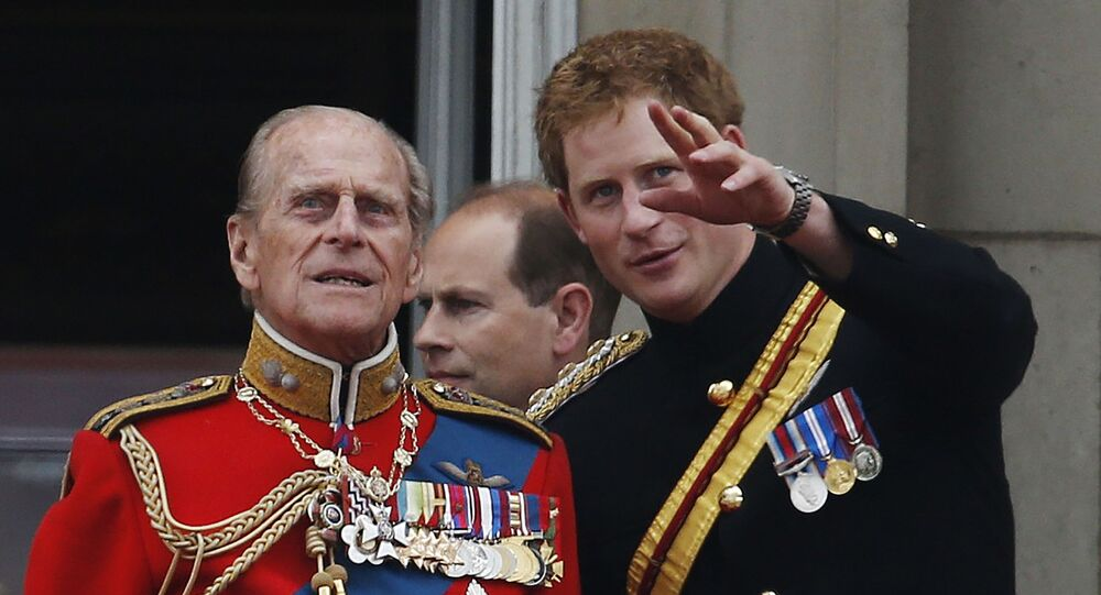 In this 14 June 2014 file photo, Britain's Prince Harry talks to Prince Philip as members of the Royal family appear on the balcony of Buckingham Palace, during the Trooping The Colour parade, in central London