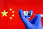 FILE PHOTO: FILE PHOTO: A woman holds a small bottle labeled with a Coronavirus COVID-19 Vaccine sticker and a medical syringe in front of displayed China flag in this illustration taken, October 30, 2020