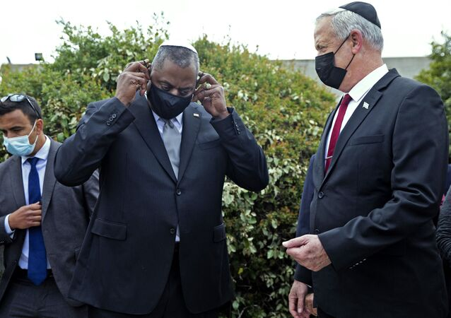 US Secretary of Defence Lloyd Austin (C) removes his mask as he stands with Israeli Defence Minister Benny Gantz (R) after a ceremony in the Hall of Remembrance at the Yad Vashem Holocaust Memorial, in Jerusalem on Monday, April 12, 2021.