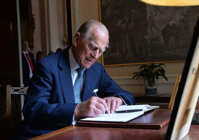 Britain's Prince Philip, The Duke of Edinburgh signs the visitors' book at Hillsborough castle in Northern Ireland on June 25, 2014.
