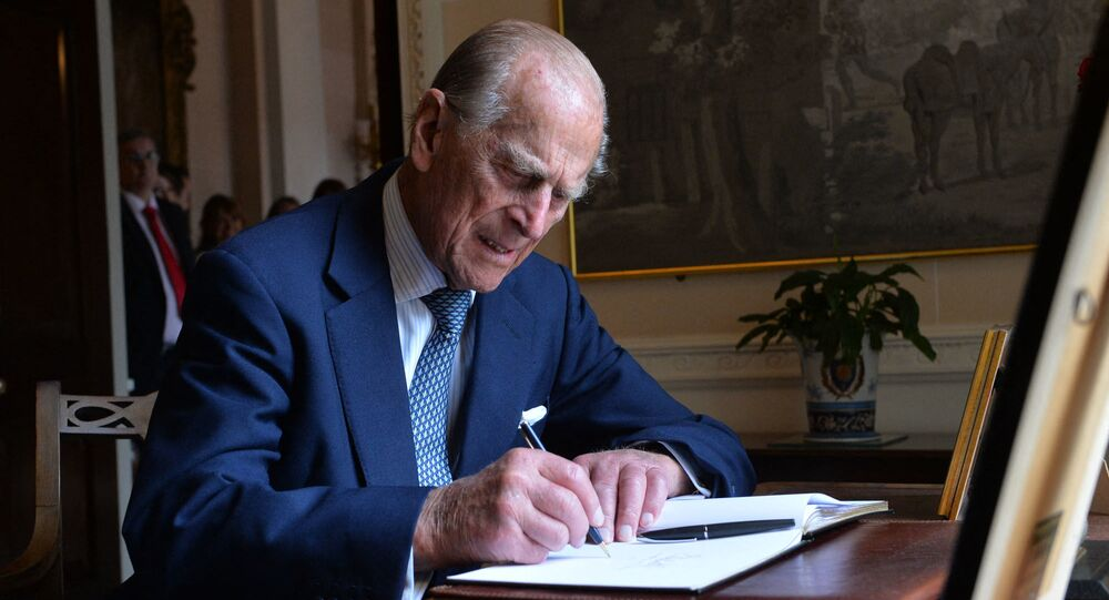 Britain's Prince Philip, The Duke of Edinburgh signs the visitors' book at Hillsborough castle in Northern Ireland on June 25, 2014.