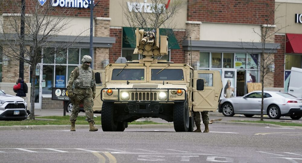 A National Guard soldier maintain watch and directs traffic at a shopping center in Brooklyn Center, Minn., a suburb of Minneapolis, Monday, April 12, 2021. A Black man died after being shot by police in a Minneapolis suburb during a traffic stop and crashing his car several blocks away, sparking violent protests that lasted into the early hours Monday as officers in riot gear clashed with demonstrators and the man's mother called for calm.