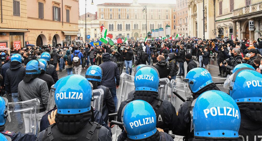 Protesters (Rear) face a line of anti-riot Police officers on April 12, 2021 on Piazza San Silvestro in central Rome during a demonstration of restaurant owners and workers, entrepreneurs and small businesses owners, demanding the easing of lockdown restrictions and financial assistance from the government, during the Covid-19 coronavirus pandemic.