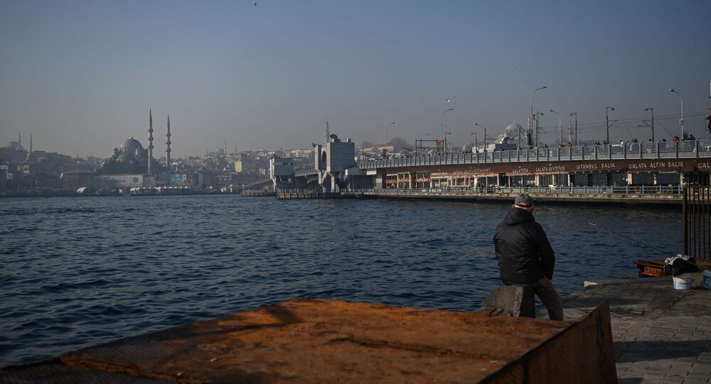 A man fishes on shore of Bosphorus straits as Galata bridge is seen in the background, at Karakoy neighbourhood, in Istanbul, on February 23, 2021.