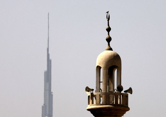 Burj Khalifa, the world's tallest tower, is silhouetted in the background of a mosque's minaret in Dubai in the United Arab Emirates, ahead of the Muslim fasting month, on April 12, 2021.