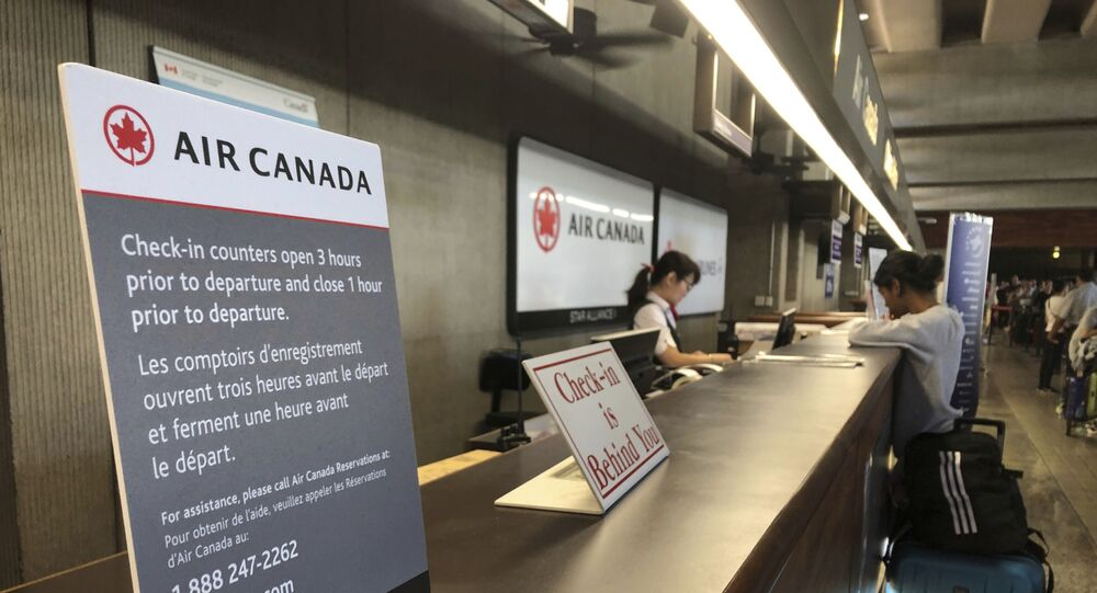 Passengers from an Australia-bound Air Canada flight diverted to Honolulu Thursday, July 11, 2019, after about 35 people were injured during turbulence, stand in line at the Air Canada counter at Daniel K. Inouye International Airport to rebook flights