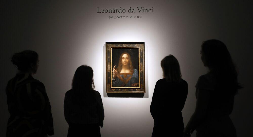 In this Oct. 24, 2017, file photo, people gather around Leonardo da Vinci's Salvator Mundi on display at Christie's auction rooms in London.