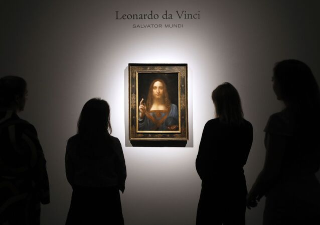 In this Oct. 24, 2017, file photo, people gather around Leonardo da Vinci's Salvator Mundi on display at Christie's auction rooms in London.