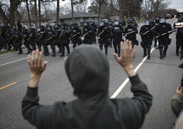 A person raises their hands as police approach near the site where a family said a man was shot and killed by local law enforcement, Sunday, April 11, 2021, in Brooklyn Center, Minn.