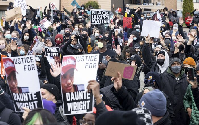 People gather before curfew holding pictures of Daunte Wright along with Black Lives Matter signs to protest his death by a police officer in Brooklyn Center, Minnesota on April 12, 2021.