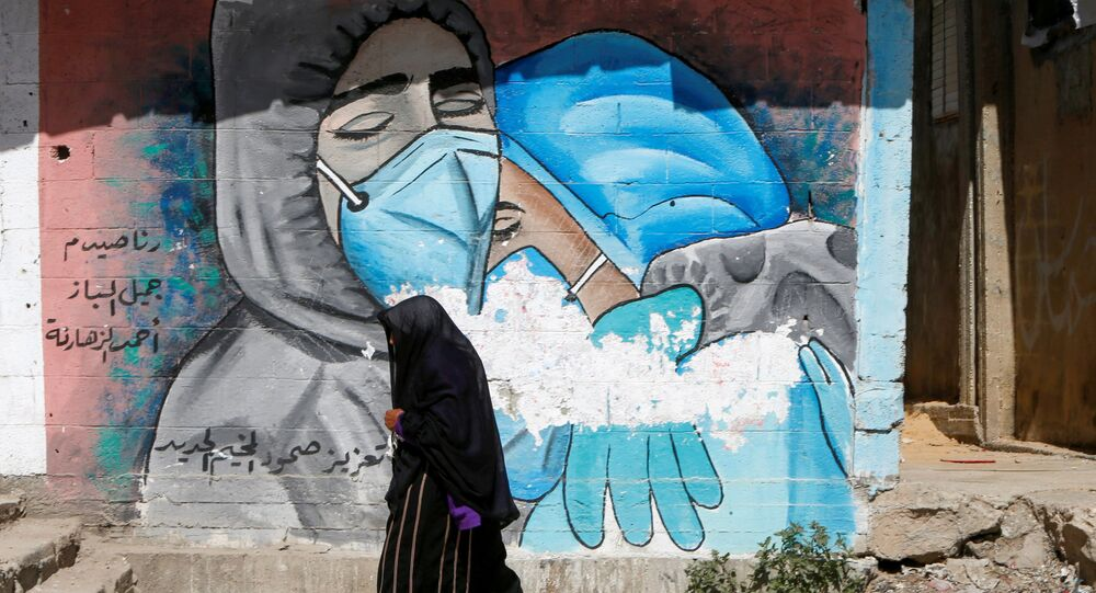 A Palestinian woman walks past a mural, amid the coronavirus disease (COVID-19) outbreak, in Gaza Strip, 17 March 2021.