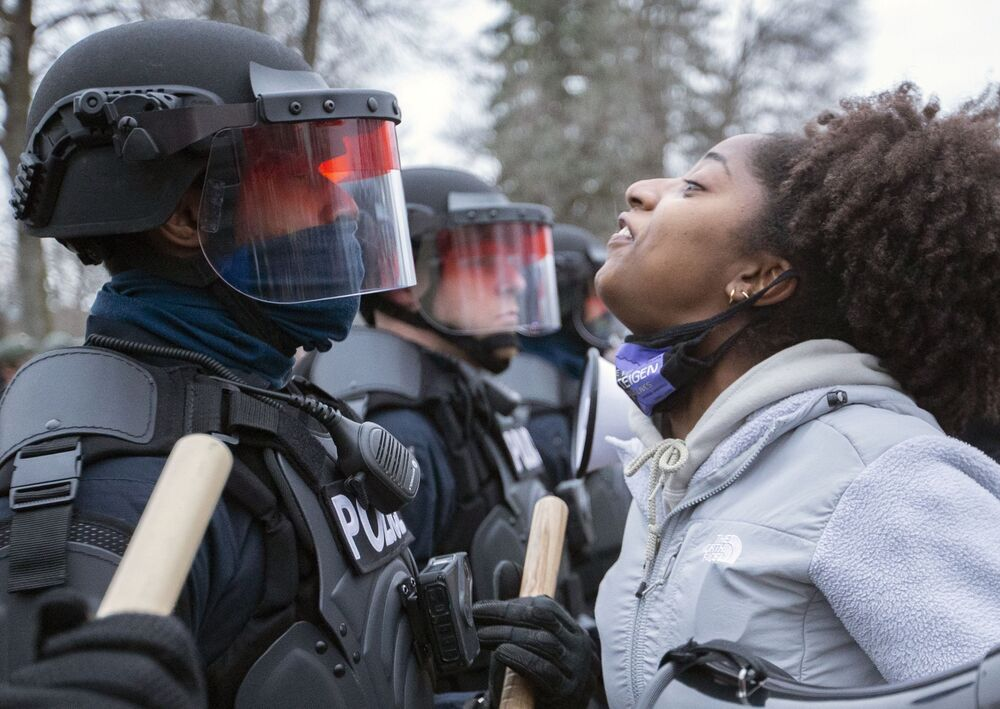 A protester and police officers in downtown Brooklyn Center, Minnesota, US.