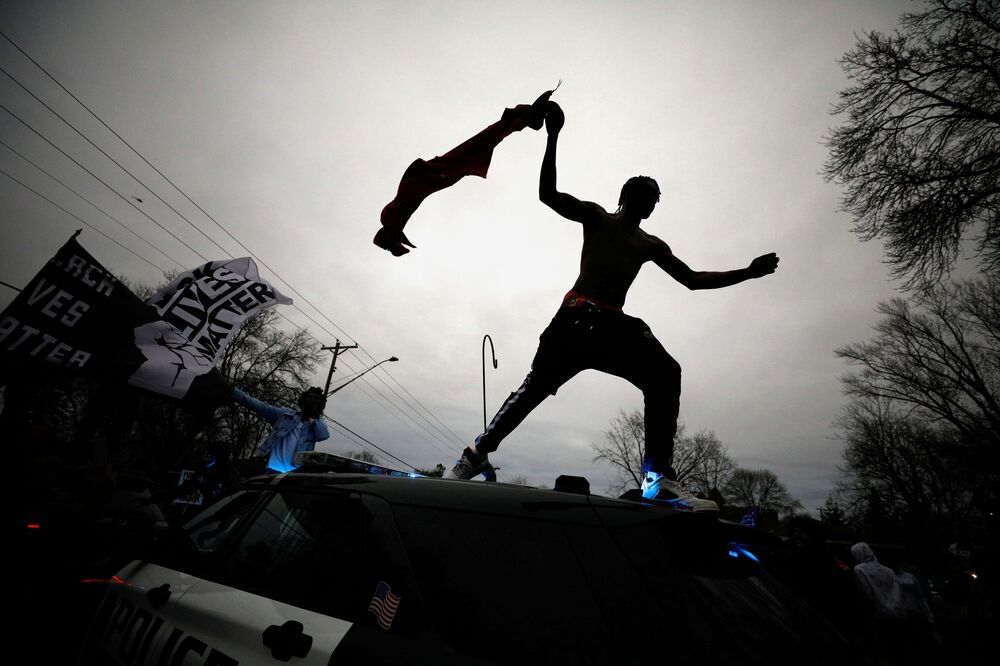 A demonstrator jumps off a police cruiser during a protest after police allegedly shot and killed a man, who local media report is identified by the victim's mother as Daunte Wright, in Brooklyn Center, Minnesota, US, 11 April 2021.
