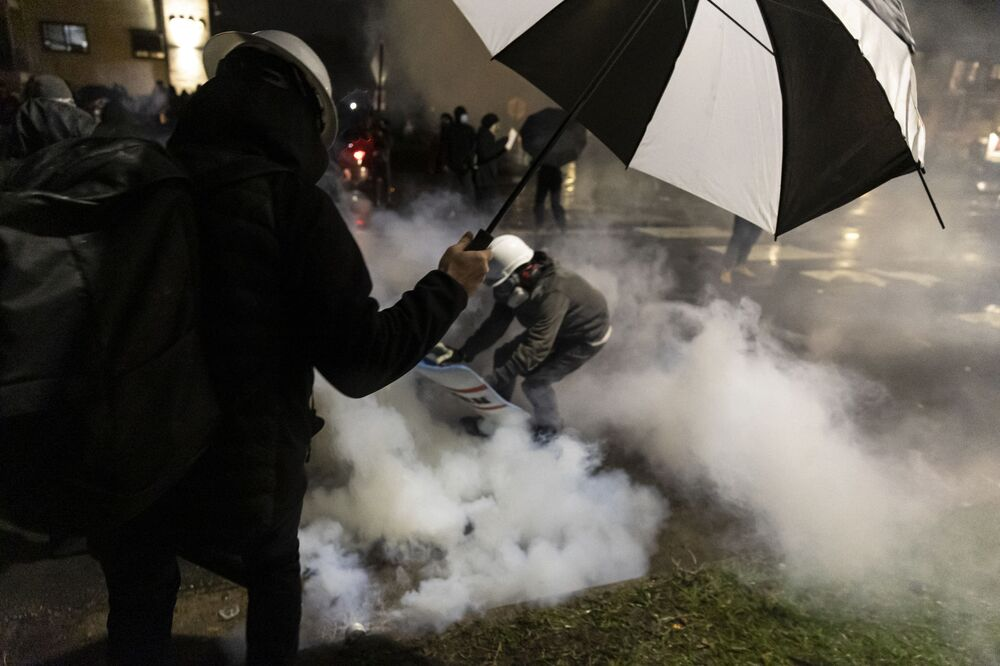 People run for cover as police fire tear gas outside the Brooklyn Center police station during a protest after a police officer shot and killed a black man in Brooklyn Center, Minneapolis, Minnesota on 12 April  2021.