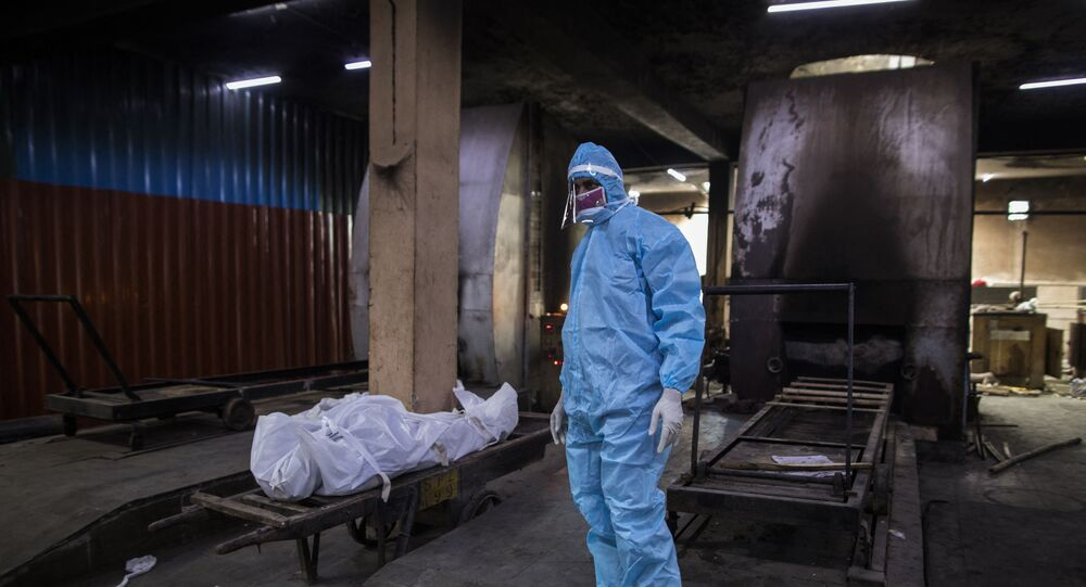 A relative wearing Personal Protective Equipment (PPE) stands next to the body of a person who died from the COVID-19 coronavirus before cremation in a furnace at the Nigambodh Ghat cremation ground, in New Delhi on 22 August 2020.