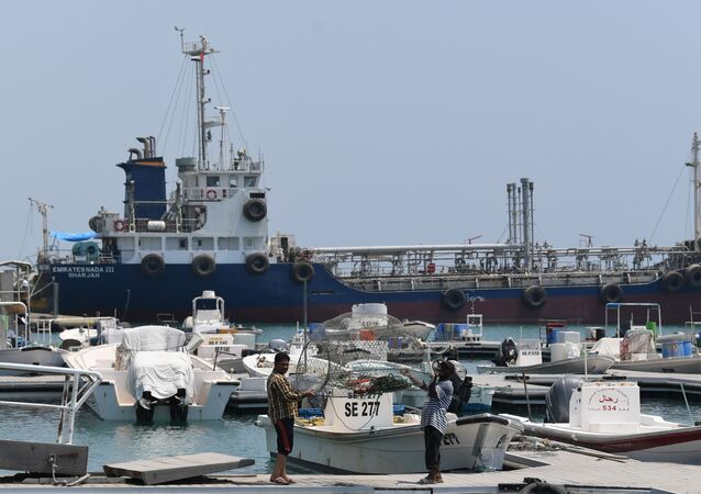 Fishermen check their net in front of ships docked in the port of Fujairah