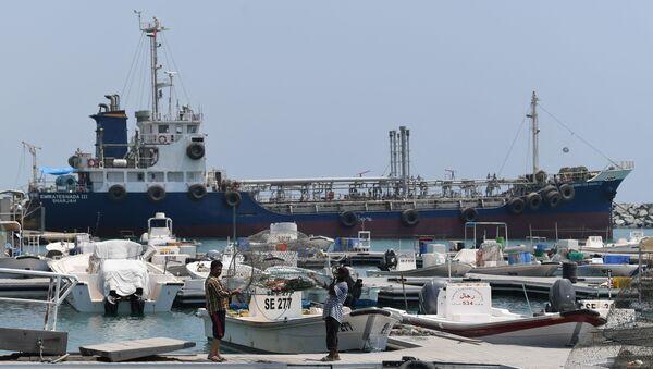 Fishermen check their net in front of ships docked in the port of Fujairah  - Sputnik International