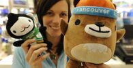 A vendor poses with the mascots (L-R) Miga and Mukmuk in a shop selling Olympic merchandise in Whistler on 7 February 2010. The two represented spirit of the 2010 Winter Olympics held in Vancouver.